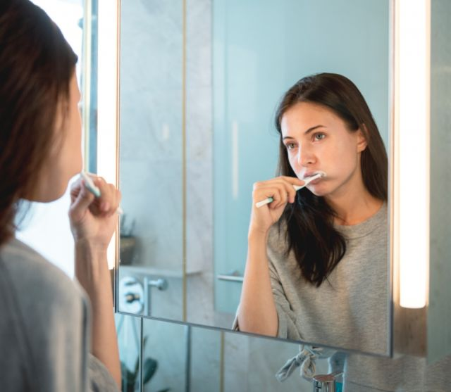 Woman's mirror reflection as she brushes her teeth - Benicia Oral Surgery, CA