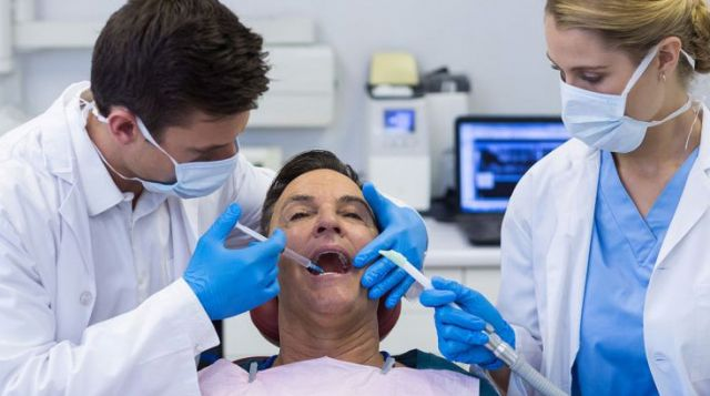 Dentist injecting anesthesia into male patient